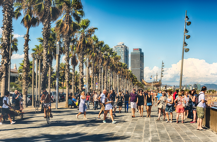 BARCELONA - AUGUST 10: People enjoying the sunny weather and walking on the promenade along Barceloneta beach, Barcelona, Catalonia, Spain, on August 10, 2017