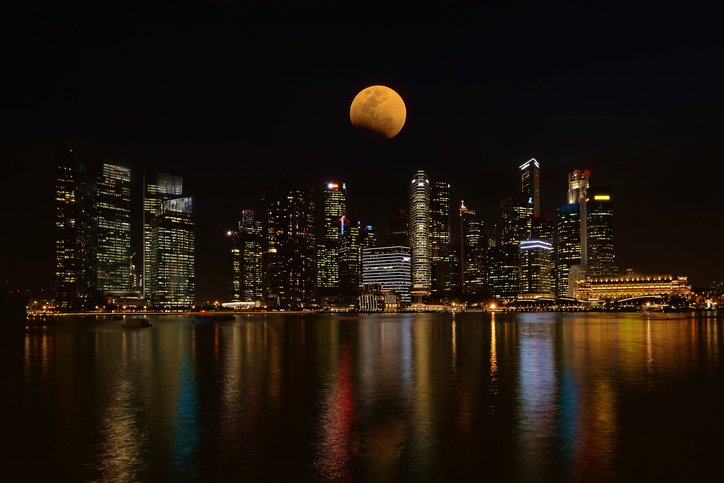 Double exposure of super full moon on night sky and city, 02-January-2018, Singapore