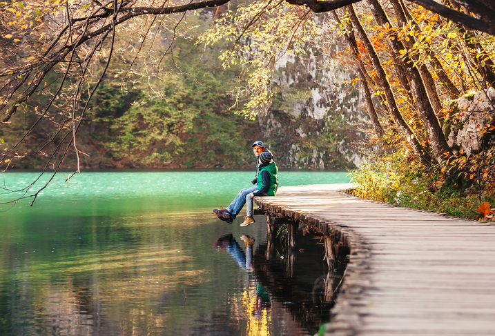 Father with son sit on bridge near the mountain lake, autumn sunny afternoon