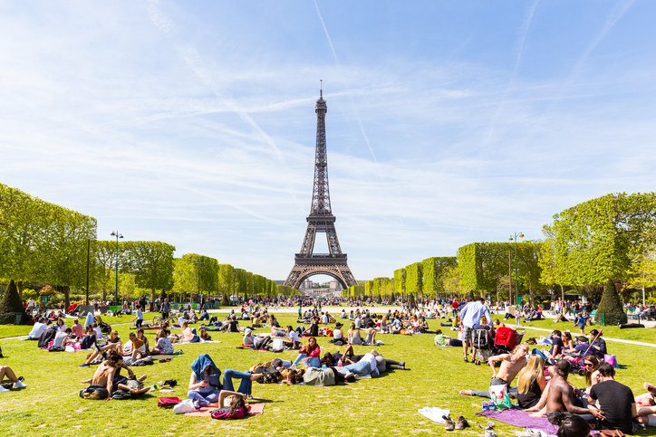 Paris, France - May 5, 2016: Lots of people relaxing and having fun on Champ de Mars with the Eiffel Tower on background on a sunny day.