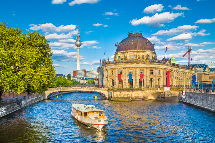 Beautiful view of Museumsinsel (Museum Island) with famous TV tower and excursion boat on Spree river in beautiful evening light at sunset, Berlin, Germany