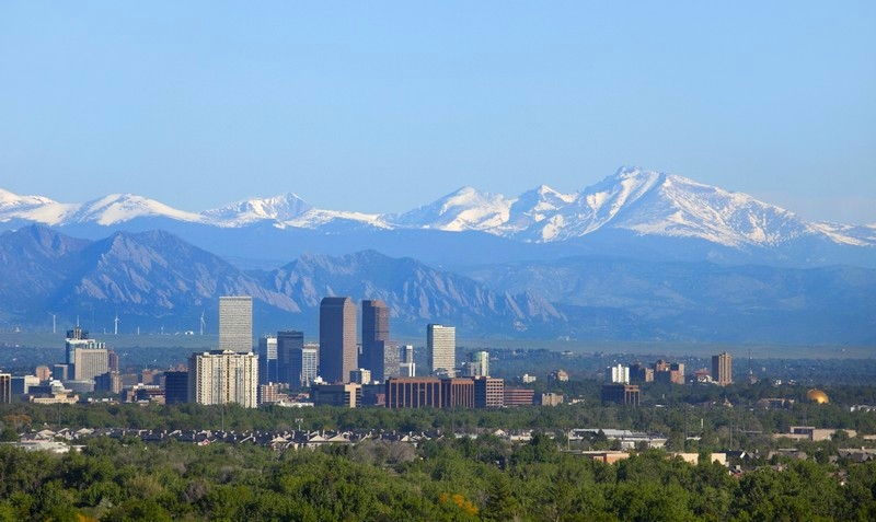 Snow covered Longs Peak, part of the Rocky Mountains stands tall in the background with the Downtown Denver skyscrapers as well as hotels, office buildings and apartment buildings filling the skyline.