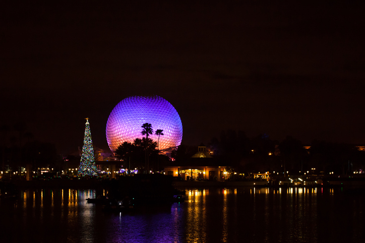 Orlando, Fl, USA- December 9, 2015:  Spaceship Earth illuminated at night with large Christmas tree viewed from the world showcase in Disney World's Epcot amusement park.
