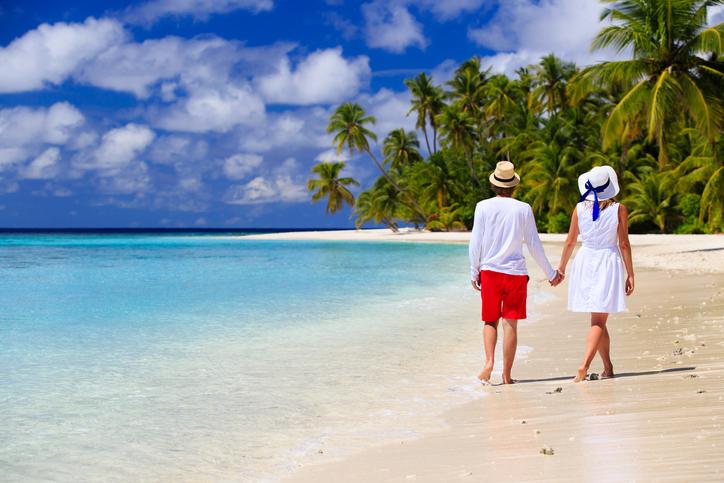happy loving couple walking on tropical beach