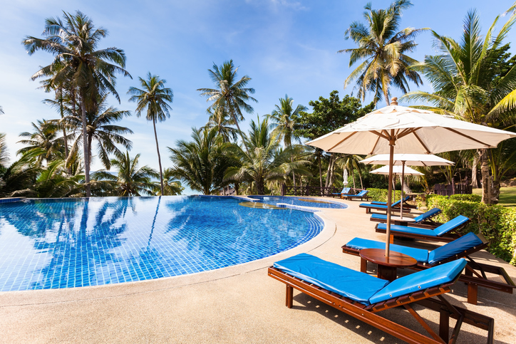 Beautiful tropical beach front hotel resort with swimming pool, sun-loungers and palm trees during a warm sunny day, paradise destination for vacations