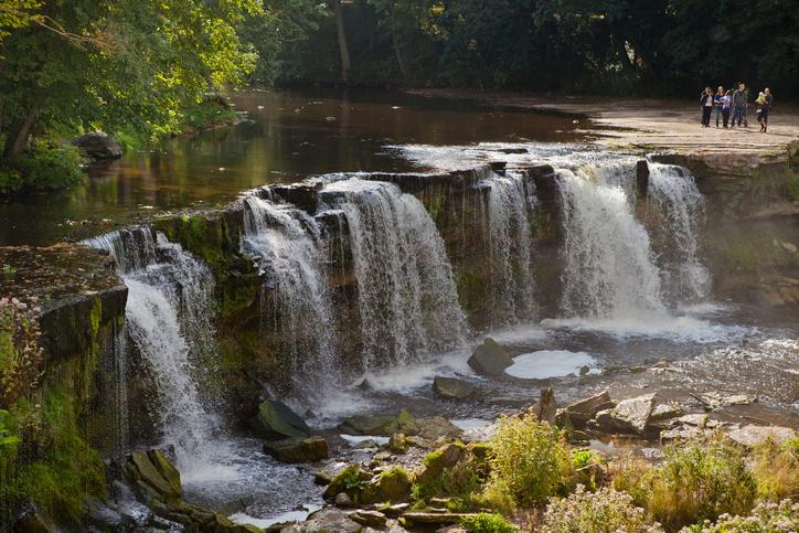 Harju Country, Estonia - September 15, 2013: Keila waterfall is third most powerful waterfall in Estonia. It is 6 meters high and 60–70 meters wide. People standing on the top of waterfall platform.
