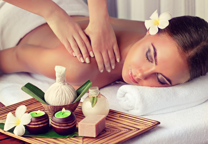 Young lady is laying on massage table and gets massage treatment.Spa and body massage.Woman is getting massage in the spa salon.