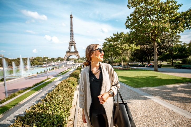 Lifestyle portrait of a young woman walking in front of the famous Eiffel tower during the sunny day in Paris