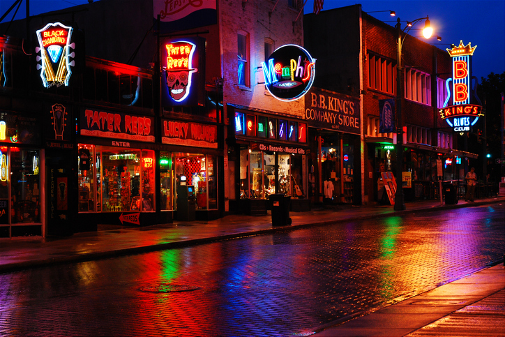 Memphis, TN, USA July 21, 2009 Beale Street in Memphis, Tennessee, lights up the streets on a rainy evening.  the street is renown for the blues bars and allowance of open drinking