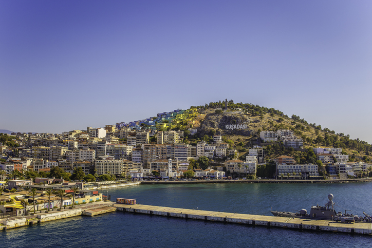 Kusadasi sign on a hill next to colourful buildings.