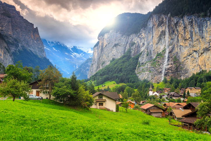 Green fields and famous touristic town with high waterfall in background,Lauterbrunnen,Bernese Oberland,Switzerland,Europe