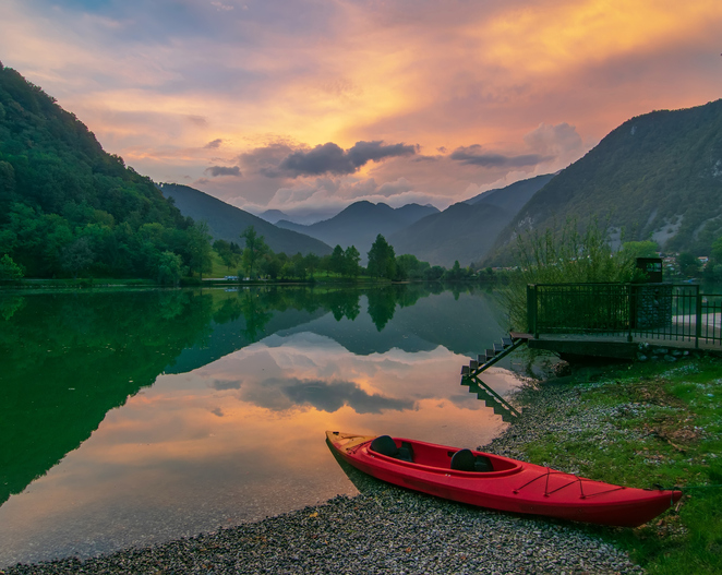Picturesque sky over reservoir on Soca river near Most na Soci, Slovenia at sunset. Red kayak on foreground. Soca river - popular place for active recreation in Julian Alps