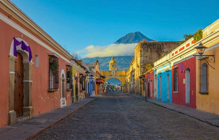The historic city of Antigua at sunrise with a view over the main street and the Catalina arch and the Agua volcano in the background, Guatemala.