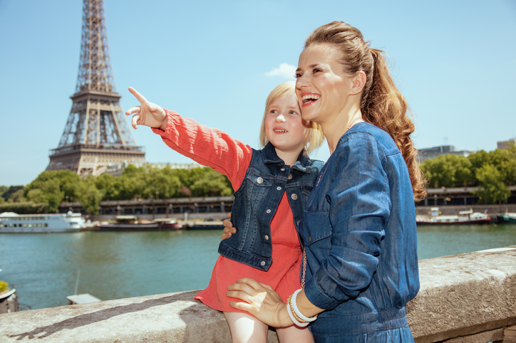 smiling trendy mother and daughter tourists near the parapet on the embankment of the river Seine overlooking Eiffel tower in Paris, France exploring attractions.