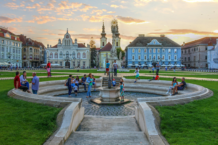 Timisoara, Romania - August 2, 2016: Sunset scene in Unirii Square (Union Square), Timisoara, Romania focusing on the central fountain with people enjoying the historic center.