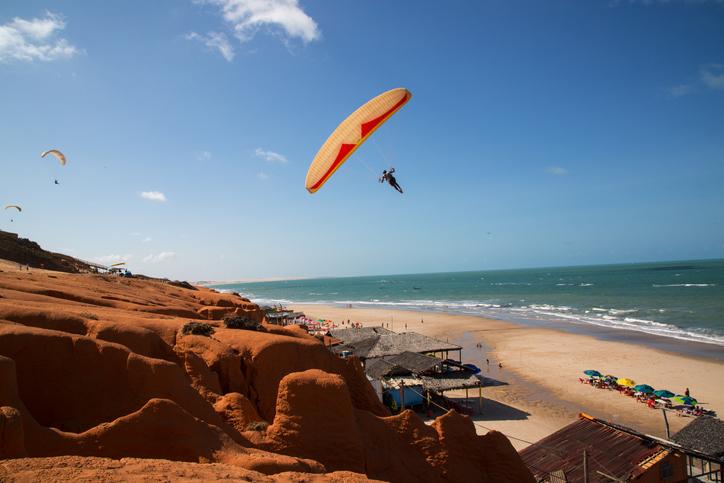 Canoa Quebrada, Ceará, Brazil - October 30, 2015: People paragliding at the Rocky Cliffs of Canoa Quebrada, Ceará, Brazil