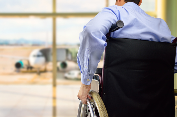 rear view of a business man in wheelchair at the airport with focus on hand