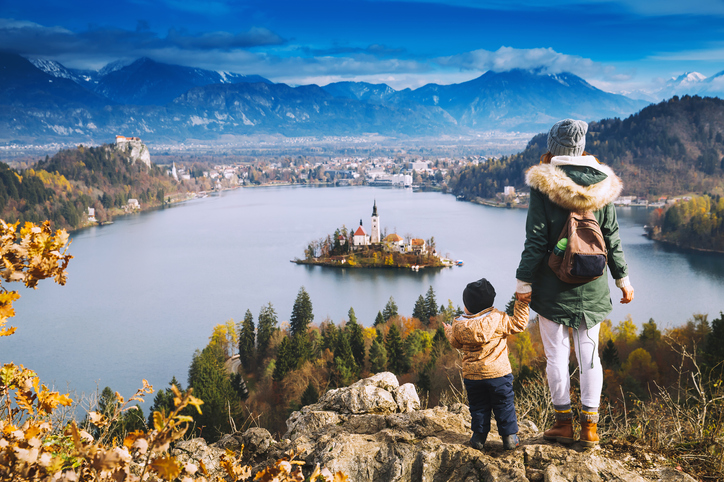 Family travel Europe. Mother with son looking on Bled Lake. Autumn or Winter in Slovenia, Europe. Top view on Island with Catholic Church in Bled Lake with Castle and Mountains in Background.