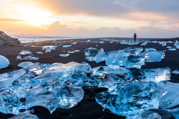 Diamond Beach in Iceland with blue icebergs melting on the black sand and ice glistening with sunrise sun light, tourist looking at beautiful arctic nature scenery, Icelandic South coast, Jokulsarlon