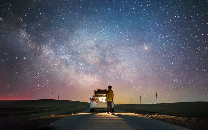 Rear view of one man glaring at the palette of milky way with car trunk open