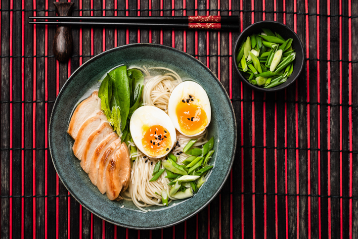 Ramen noodle soup with chicken and egg on bamboo mat. Table top view. Asian cuisine food