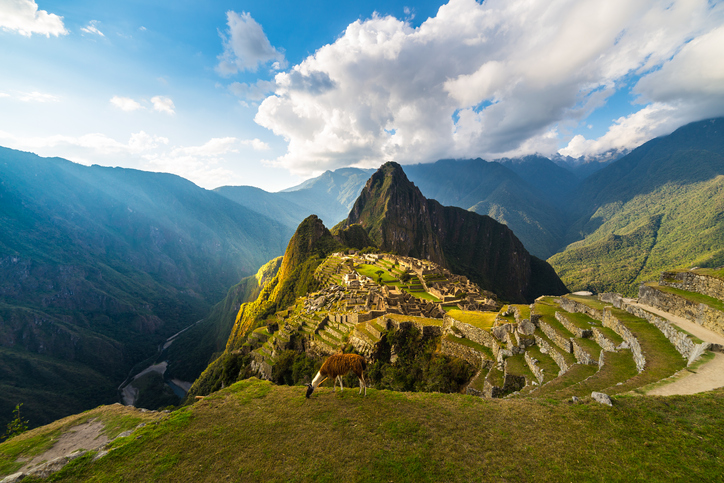 Machu Picchu illuminated by the warm sunset light. Wide angle view from the terraces above with scenic sky and sun burst. Dreamlike travel destination, world wonder. Cusco Region, Peru.