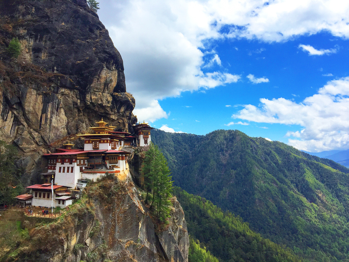 View of the spectacular Tiger's Nest Monastery (Taktsang Palphug Monastery) on a cliff of the Paro Valley in Bhutan. The Tiger's nest is a prominent and difficult to access Himalayan Buddhist holy site first built in 1692 around the Taktsang Senge Samdup cave where Guru Padmasambhava, who introduced Buddhism to Bhutan, meditated for three years. Paro (Dzongkha) is an ancient town in the homonymous valley, with many sacred sites, temples and historical buildings. Bhutan is famous for pioneering the concept of Gross National Happiness.