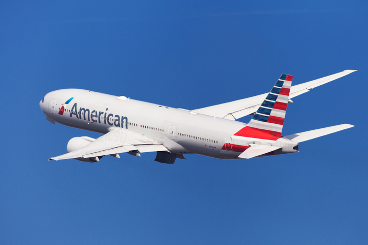 Barcelona, Spain - August 21, 2018: American Airlines Boeing 777-200ER banking left after taking off from El Prat Airport in Barcelona, Spain.