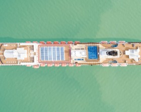 Cruise ship at harbor. Aerial view of beautiful large white liner at sunrise. Top view luxury cruise.