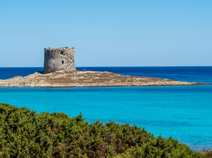 View of La Pelosa Beach. In the background, the landmark 16th century La Pelosa Tower (Italian: Torre della Pelosa).