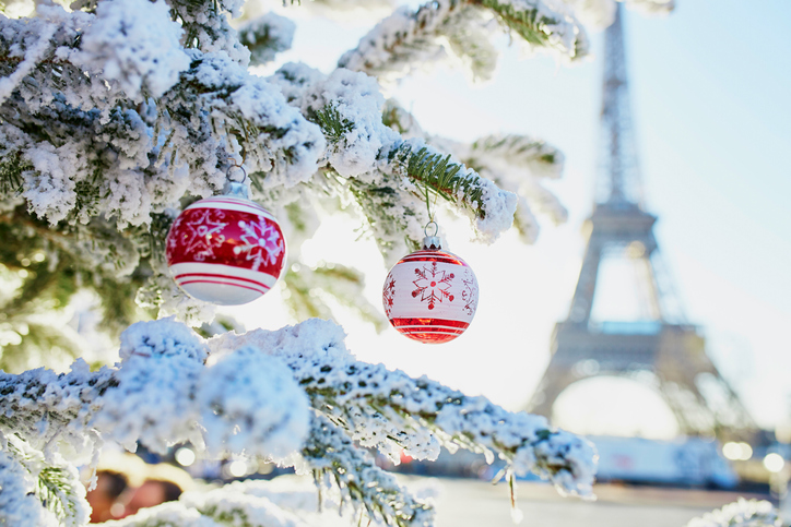 Christmas tree covered with snow and decorated with red toys near the Eiffel tower in Paris, France