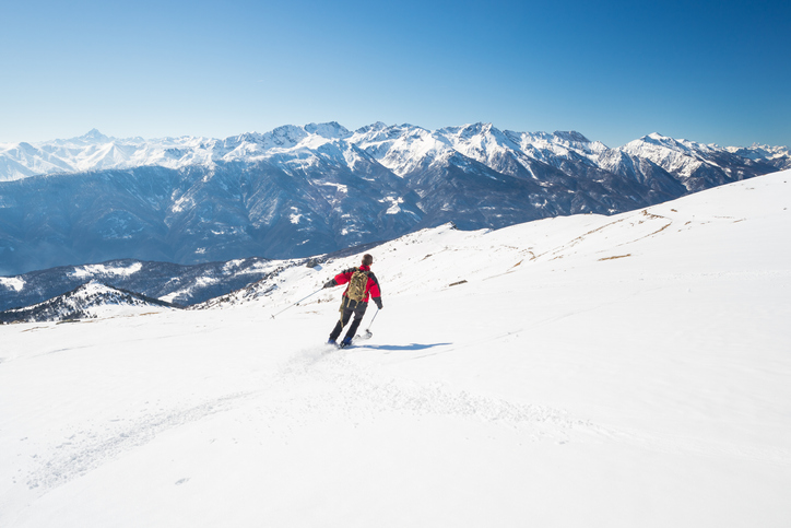 One person skiing downhills on snowy slope in scenic ski resort of the italian Alps, with bright sunny day of late winter season. Majestic mountain peaks in the background.