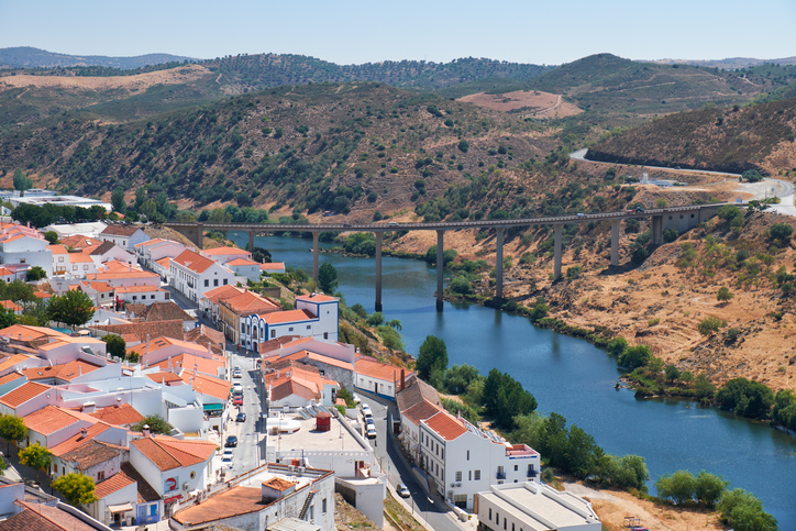 MERTOLA, PORTUGAL - JUNE 30, 2016:   The view of Mertola city on the riverside of Guadiana with the bridge over the river on the background. Baixo Alentejo. Portugal
