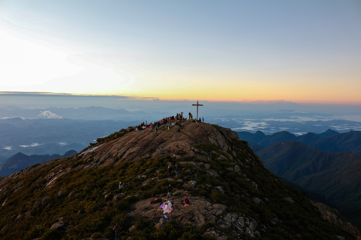 Alto Caparaó, ES, Brazil - August 03, 2015: Sunrise on Pico da Bandeira, the third highest point in Brazil. People going toward the flat spot to contemplate the beautiful look that occurs at sunrise. Photo taken from a radio tower located high on the mountain.