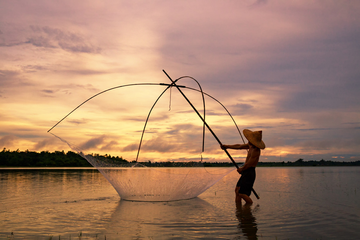 Fisherman on silhouette sunrise with gear fishing on the lake is a culture of Thai or Laos people's