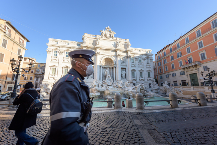 ROME, ITALY - 10 March 2020: A city Police man wearing a face mask walks across the deserted Trevi Fountain square, Rome, Italy. As of today, the Italian government decreeted a nationwide quarantine, with travel and gatherings bans, limited opening hours for shops and venues, and emergency health measures following the CoVid-19 epidemic. Tourism has collapsed as a result.