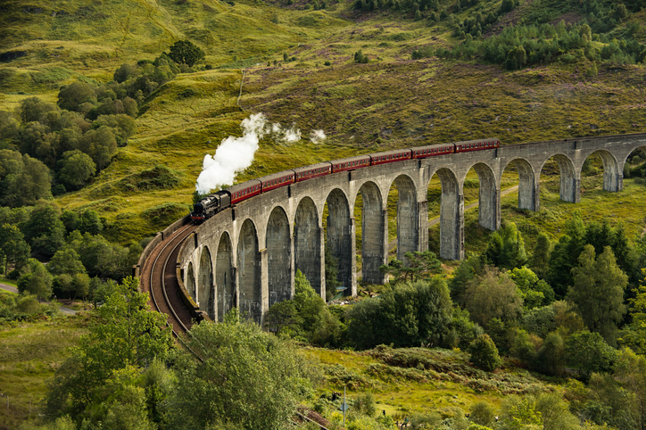 The Jacobite steam train passing the Glenfinnan Viaduct in Scotland