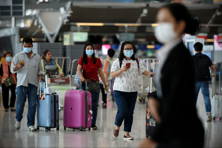 Bangkok, Thailand - February 18, 2020: Air travelers wearing masks walk through departures hall of Suvarnabhumi Airport. Thailand has been assessed as a country at risk of Covid-19 outside of China.
