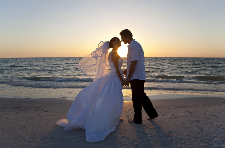 A married couple, bride and groom, kissing at sunset on a beautiful tropical beach