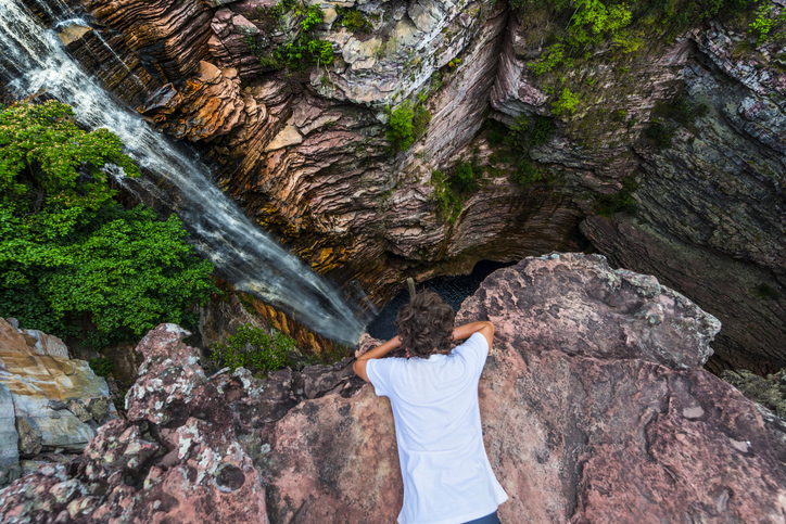 Boy looking down in a canyon with a waterfall