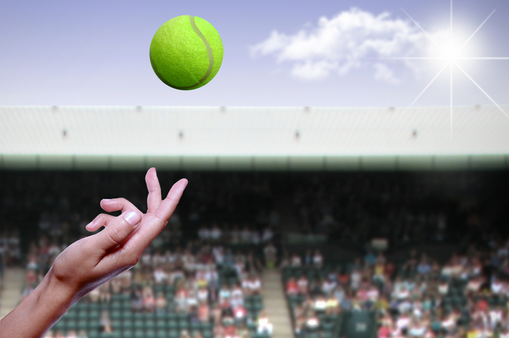 Tennis ball being tossed in the air during a match