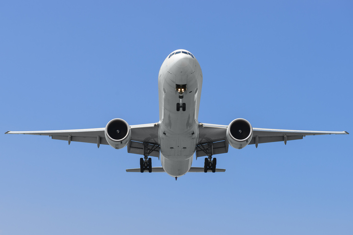 Commercial airplane on finals runway against blue sky.