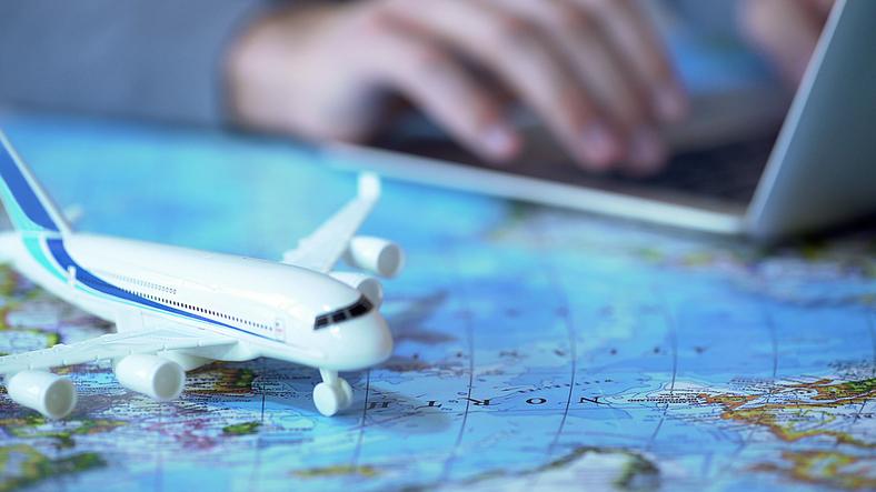 Airplane model closeup, defocused person booking flight tickets online on laptop