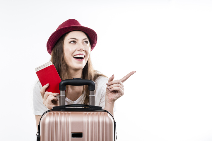 Beautiful happy woman sitting holding her luggage, passport, map and ticket for boarding. Air flight journey concept.