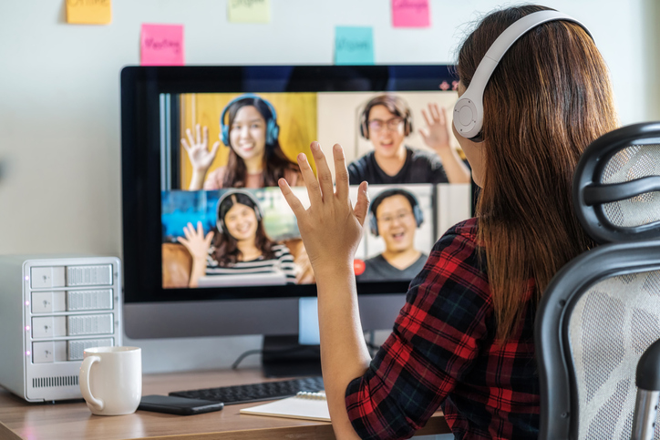 Online meeting, Social distancing and new normal concept, Rear View of Asian Business woman say hello with teamwork colleague in video conference when Coronavirus outbreak