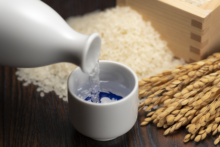 Cold sake with rice and ear of rice on the table