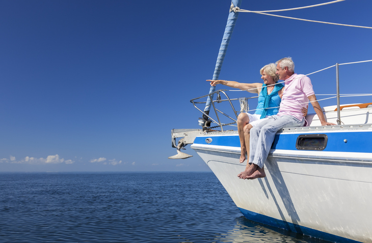 A happy senior couple sitting on the side of a sail boat on a calm blue sea looking and pointing to a clear horizon