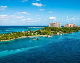 Bright and vibrant panoramic image with Paradise Island and palm trees close at the cruise port of Nassau in the Bahamas. Blue sky and some white clouds. Wide image.