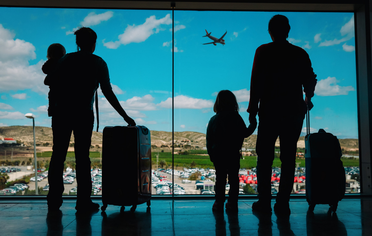 family with kids and luggage looking at planes in airport, travel concept