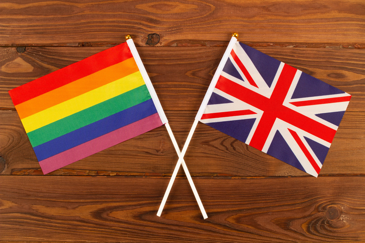 Rainbow flag LGBT and flag of Great Britain on brown wood planks background. LGBT Pride Month. LGBTQ. LGBTQIA. Close Up. Top view